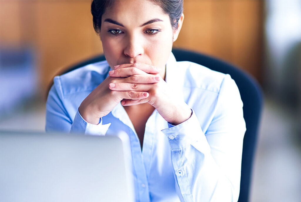 Photograph of a concerned woman looking at a laptop