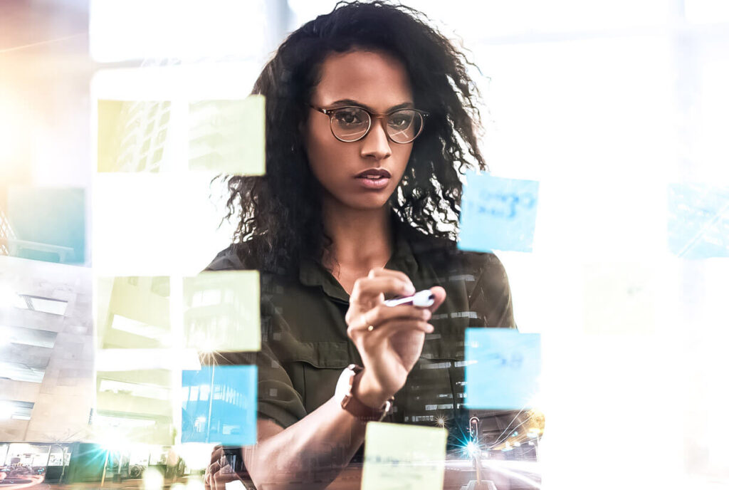 Photo of a woman in an office writing on a glass wall
