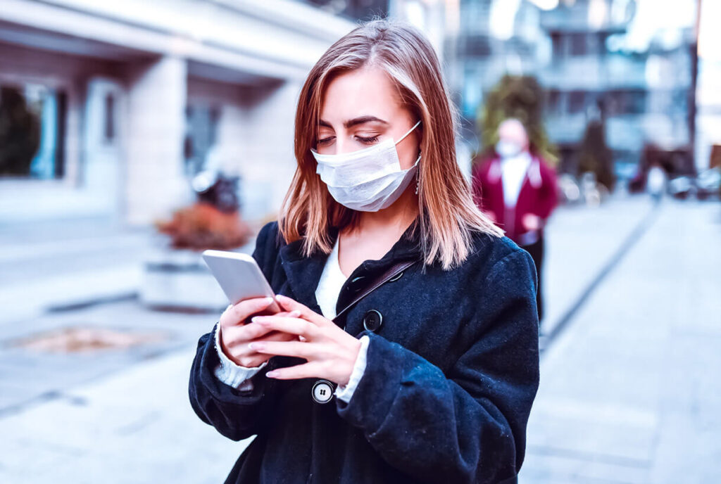 A woman wearing a mask and using a smart phone