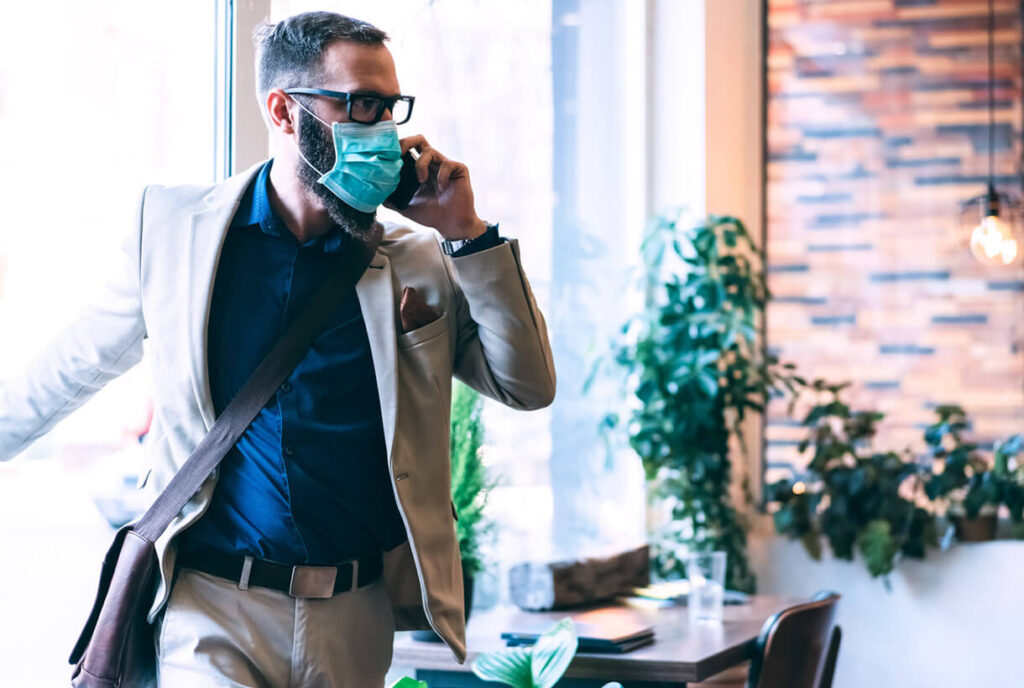 Photo of a man walking into an office wearing a mask and using a smart phone